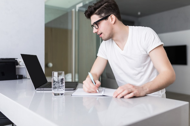 ノートパソコンを机に取り組んでいるハンサムな若い男。