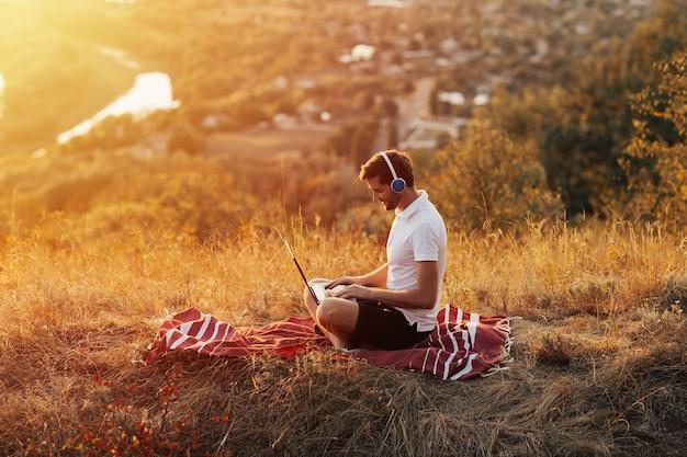 노트북에서 작업 하 고 언덕에 야외에서 앉아있는 동안 웃 고 잘 생긴 젊은 남자.
