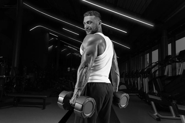 Красивый молодой человек, работающий с гантелями в тренажерном зале. прокачка плеча. концепция фитнеса и бодибилдинга.