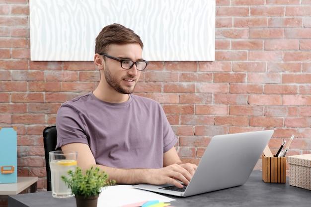 オフィスでラップトップを使用して作業しているハンサムな若い男