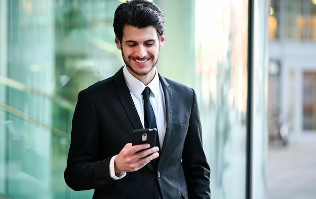 Красивый молодой менеджер, используя смартфон на открытом воздухе