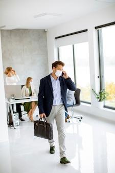 Красивый молодой человек гуляет и пользуется мобильным телефоном в защитных масках, чтобы предотвратить коронавирус в офисе