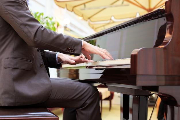 Красивые молодые люди играют на пианино