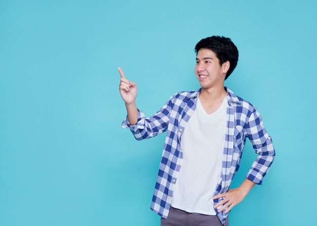 Handsome young men pointing on blue wall