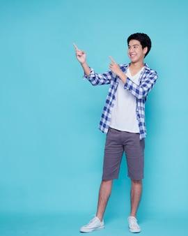 파란 벽에 가리키는 잘 생긴 젊은 남자