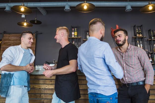 ハンサムな若い男たちが互いに話すバーカウンターに立っている