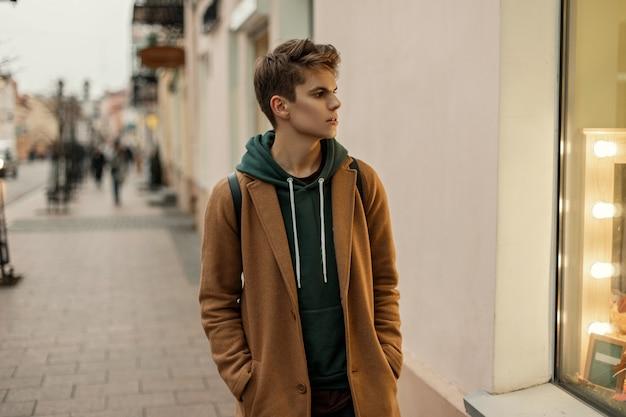 까마귀와 트렌디 한 코트에있는 남자의 잘 생긴 젊은 모델은 상점 창 근처의 도시에서 산책