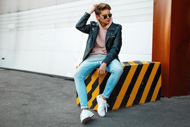검은 가죽 재킷, 분홍색 셔츠, 청바지와 흰색 신발에 선글라스를 착용 한 남자의 잘 생긴 젊은 모델은 검은 색과 노란색 슬래브에 앉아있다.