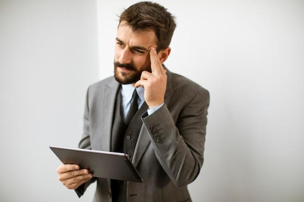 Красивый молодой современный бизнесмен с помощью цифрового планшета в офисе