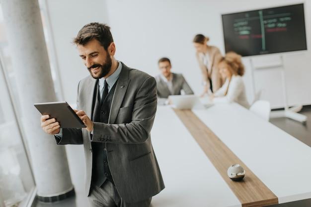 Красивый молодой современный бизнесмен с помощью цифрового планшета в офисе Premium Фотографии
