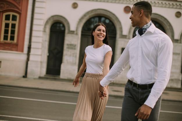 Красивая молодая многонациональная пара гуляет по улице