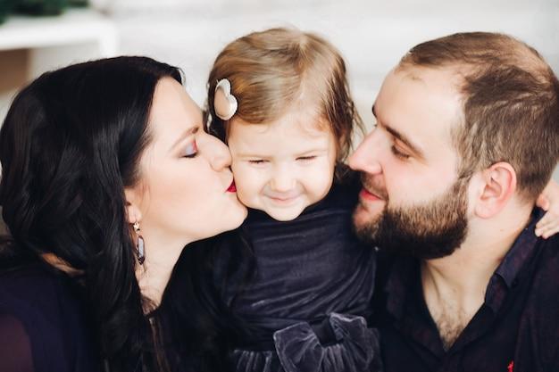 長い黒のウェーブのかかった髪のハンサムな若いお母さん、短い黒髪の魅力的な強いお父さんと子供