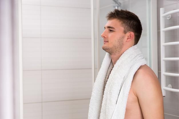 현대적인 타일 욕실에 서 있는 동안 절차를 씻은 후 어깨에 수건을 들고 있는 잘생긴 젊은 근육질의 남자