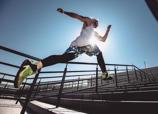 現代のスポーツ服を着たハンサムな若い筋肉質の男は、明るい晴れた日に屋外の階段を駆け上がります。ジョギングをしている男性の広角写真。スポーツライフスタイル。