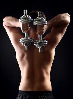 Красивый молодой мускулистый спортсмен выполняет упражнение с гантелями на темном фоне