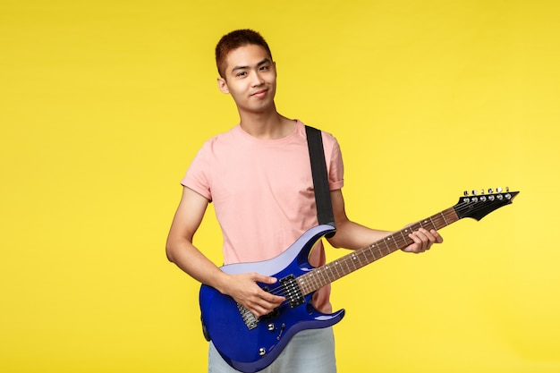 Handsome young musician playing the guitar and singing, isolated