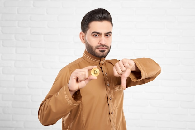 Handsome young muslim male being sad and upset holding golden bitcoin and showing thumbs down