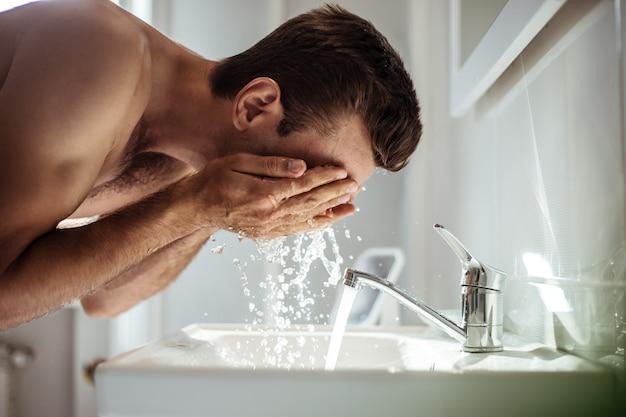 ハンサムな若い裸の男が自宅のバスルームで顔を洗っています。