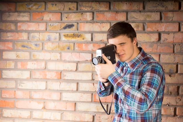 Handsome young photographer in casual long sleeve shirt capturing something using camera on brick wall background.
