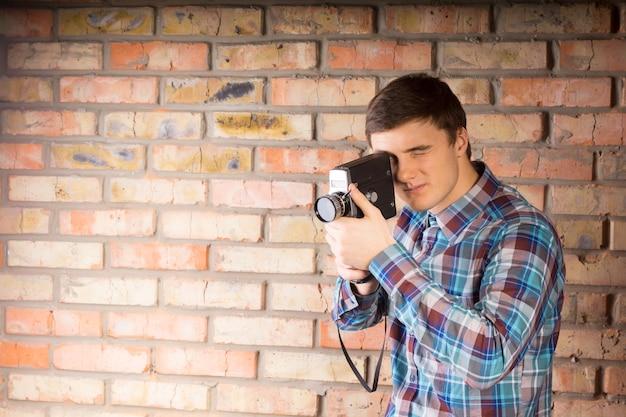 벽돌 벽 배경에서 카메라를 사용하여 무언가를 포착하는 캐주얼 긴 소매 셔츠를 입은 잘생긴 젊은 사진작가.