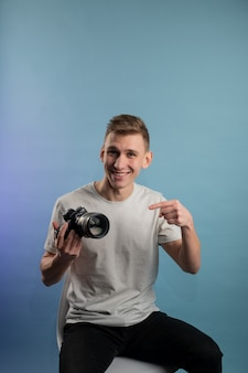 Handsome young photographer using camera on blue background.man using a professional camera.portrait of guy looking at photo camera
