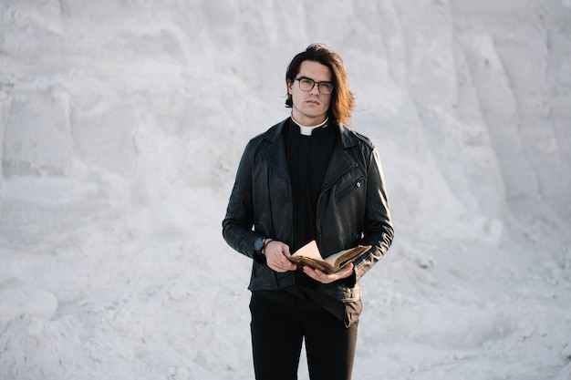 Handsome young priest portrait outside at sunset. he is wearing eye glasses and roman collar shirt and a leather jacket.