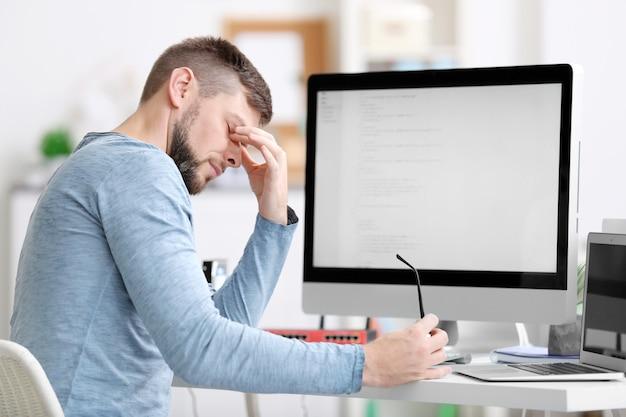 사무실에서 일하는 잘 생긴 젊은 프로그래머
