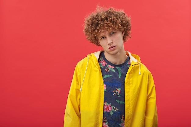 黄色のレインコートに身を包んだ美しい顔を持つハンサムな若い赤毛の男