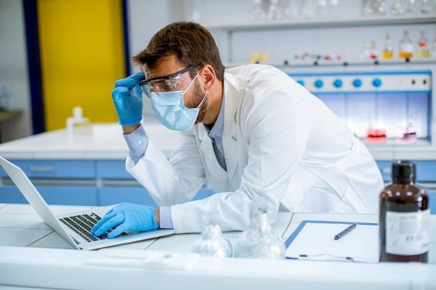 Красивый молодой исследователь в белом лабораторном халате и защитной маске работает с ноутбуком, сидя в лаборатории