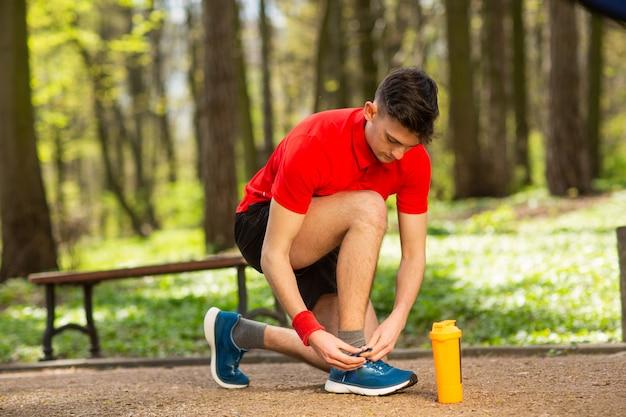 Красивый молодой бегун, связывая шнурки на дорожке в парке весны. рядом с ним оранжевая термопара