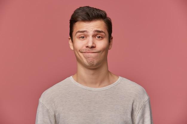 Красивый молодой грустный парень с поднятыми бровями носит пустую футболку, недоверчиво смотрит в камеру, стоит на розовом фоне.