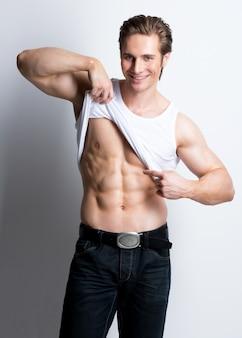 白いシャツを着たハンサムな若いセクシーな男は、白い壁の上に胴体のポーズを示した。