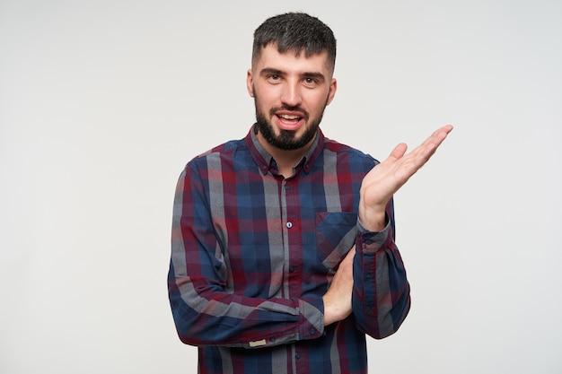 Bel giovane ragazzo barbuto dai capelli corti bruna alzando perplesso il palmo della mano mentre guarda emotivamente, vestito con una camicia a scacchi mentre posa sul muro bianco