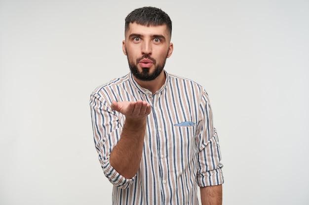 Bel giovane ragazzo bruna dai capelli corti con la barba che alza il palmo e soffia un bacio d'aria, indossa una camicia a righe mentre si trova sul muro bianco