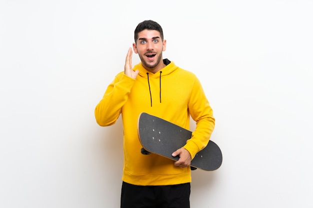 Handsome young skater man over isolated white wall with surprise and shocked facial expression
