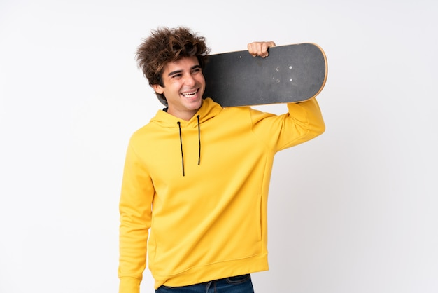 Handsome young skater man over isolated white wall
