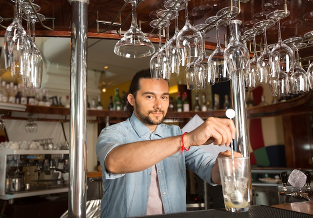Handsome young smiling bartender holding steel swizzle spoon in the glass with ice.