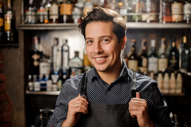 Handsome and young smiling brown haired barman