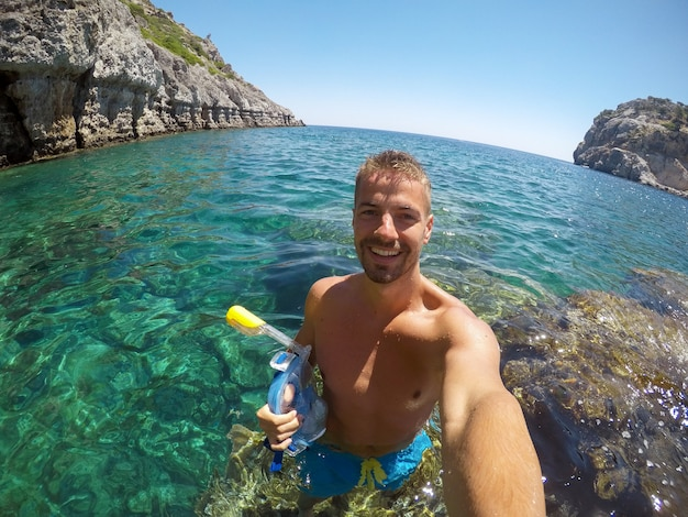 Handsome young smiling touristic man enjoying a sunny day and taking a selfie with a mobile while standing on the stone in the sea and holding snorkelling mask.