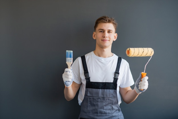 Handsome young smiling worker with paint roller and brush on gray background