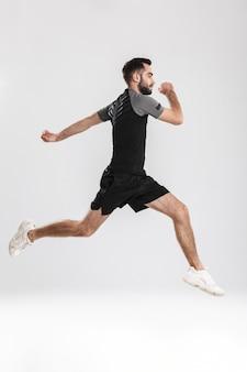 ジャンプするハンサムな若いスポーツフィットネス男。