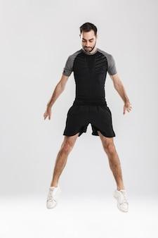ハンサムな若いスポーツフィットネス男ポーズ、ジャンプ。