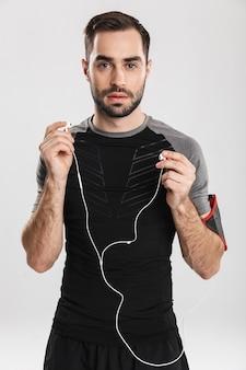 ハンサムな若いスポーツフィットネスの男性がポーズをとって、イヤホンで音楽を聴いています。