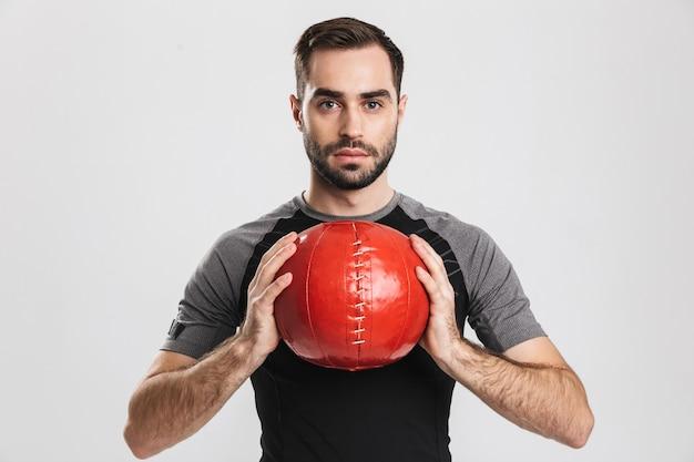 잘생긴 젊은 스포츠 피트 니스 남자 포즈, 공으로 운동을 확인 합니다.