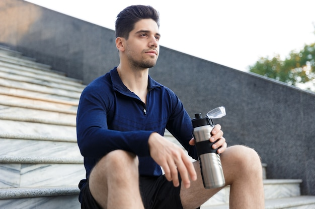 Handsome young sportsman drinking water from a bottle outdoors, sitting on staircase