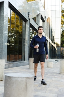 Handsome young sportsman drinking water from a bottle outdoors, walking