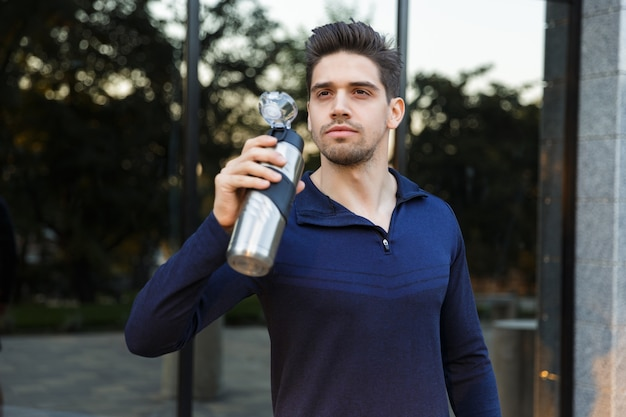 Handsome young sportsman drinking water from a bottle outdoors