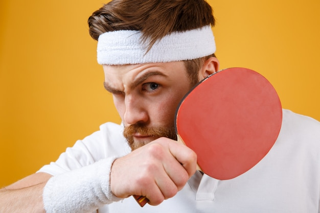 Красивый молодой спортсмен держит ракетку для настольного тенниса