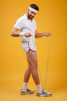 Handsome young sportsman holding skipping rope