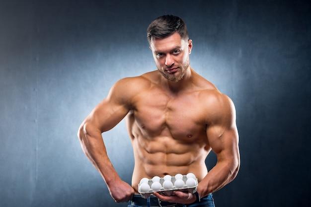 Красивый молодой спортсмен держит упаковку с яйцами